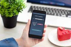 Θηλυκά χέρια που κρατούν το τηλέφωνο με app τις σε απευθείας σύνδεση αγορές και το σημειωματάριο Στοκ εικόνα με δικαίωμα ελεύθερης χρήσης