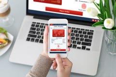 Θηλυκά χέρια που κρατούν το τηλέφωνο με app τις σε απευθείας σύνδεση αγορές κοντά στο lap-top Στοκ εικόνα με δικαίωμα ελεύθερης χρήσης