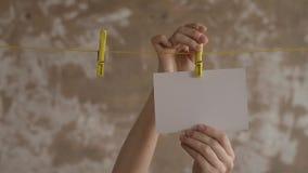 Θηλυκά χέρια που κρεμούν τις κάρτες στους ένδυμα-γόμφους απόθεμα βίντεο