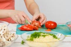 Θηλυκά χέρια που κόβουν την ντομάτα στον πίνακα κουζινών Στοκ Εικόνες