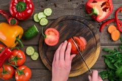 Θηλυκά χέρια που κόβουν την ντομάτα στον πίνακα, τοπ άποψη Στοκ Φωτογραφία