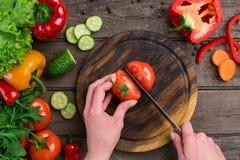 Θηλυκά χέρια που κόβουν την ντομάτα στον πίνακα, τοπ άποψη Στοκ Εικόνες