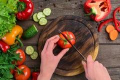 Θηλυκά χέρια που κόβουν την ντομάτα στον πίνακα, τοπ άποψη Στοκ φωτογραφία με δικαίωμα ελεύθερης χρήσης