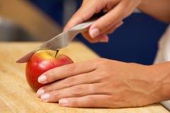 Θηλυκά χέρια που κόβουν το μήλο με το μαχαίρι Στοκ Φωτογραφίες