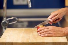 Θηλυκά χέρια που κόβουν το μήλο στον τεμαχίζοντας πίνακα Στοκ φωτογραφία με δικαίωμα ελεύθερης χρήσης