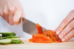 Θηλυκά χέρια που κόβουν το φρέσκες αγγούρι και την ντομάτα Στοκ εικόνα με δικαίωμα ελεύθερης χρήσης