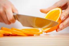 Θηλυκά χέρια που κόβουν το φρέσκο juicy πορτοκάλι Στοκ Φωτογραφίες