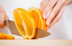 Θηλυκά χέρια που κόβουν το φρέσκο juicy πορτοκάλι Στοκ εικόνα με δικαίωμα ελεύθερης χρήσης