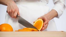 Θηλυκά χέρια που κόβουν το φρέσκο juicy πορτοκάλι Στοκ φωτογραφίες με δικαίωμα ελεύθερης χρήσης