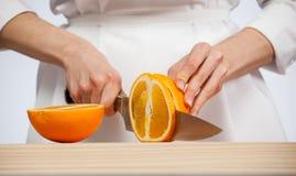 Θηλυκά χέρια που κόβουν το φρέσκο juicy πορτοκάλι Στοκ εικόνες με δικαίωμα ελεύθερης χρήσης