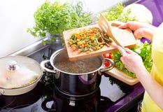Θηλυκά χέρια που μαγειρεύουν τη φυτική σούπα Στοκ Εικόνες