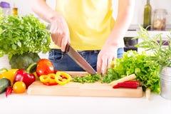 Θηλυκά χέρια που προετοιμάζουν τη φυτική σαλάτα στην κουζίνα Στοκ Φωτογραφία