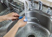 Θηλυκά χέρια που πλένουν το ενιαίο μικρό μαχαίρι στο νεροχύτη κουζινών Στοκ φωτογραφίες με δικαίωμα ελεύθερης χρήσης