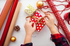 Θηλυκά χέρια που τυλίγουν τα δώρα Χριστουγέννων στο έγγραφο και που εμπλέκουν τα WI Στοκ Φωτογραφία
