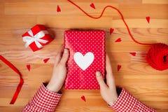 Θηλυκά χέρια που τυλίγουν το δώρο στον ξύλινο πίνακα Στοκ εικόνες με δικαίωμα ελεύθερης χρήσης