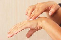 Θηλυκά χέρια που χρησιμοποιούν την καλλυντική κρέμα δερμάτων Στοκ Εικόνες
