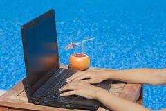 Θηλυκά χέρια στο πληκτρολόγιο lap-top στο poolside στοκ εικόνες