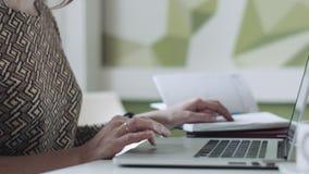 Θηλυκά χέρια συγκομιδών που χρησιμοποιούν το ημερολόγιο και το lap-top απόθεμα βίντεο