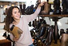 Θηλυκά χειμερινά θηλυκά παπούτσια αγοράς στο κατάστημα παπουτσιών Στοκ Εικόνες
