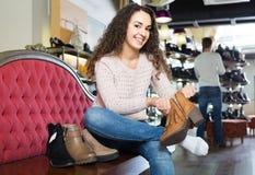 Θηλυκά χειμερινά θηλυκά παπούτσια αγοράς στο κατάστημα παπουτσιών Στοκ Φωτογραφία