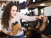 Θηλυκά χειμερινά θηλυκά παπούτσια αγοράς στο κατάστημα παπουτσιών Στοκ Εικόνα