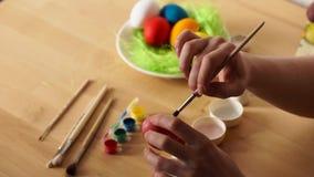 Θηλυκά χρωματισμένα χέρι αυγά Πάσχας με μια βούρτσα φιλμ μικρού μήκους