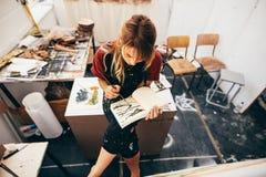 Θηλυκές εικόνες σχεδίων καλλιτεχνών στο εργαστήριό της Στοκ εικόνα με δικαίωμα ελεύθερης χρήσης