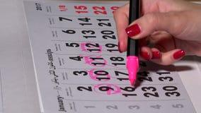 Θηλυκές εργάσιμες ημέρες προγραμματισμού χεριών με το ρόδινο δείκτη στο ημερολόγιο απόθεμα βίντεο