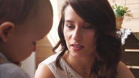 Θηλυκές πρότυπες συζητήσεις προσώπου στο γιο της σε έναν βλαστό φωτογραφιών απόθεμα βίντεο