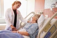 Θηλυκές συζητήσεις γιατρών στον ανώτερο θηλυκό ασθενή στο νοσοκομειακό κρεβάτι Στοκ Φωτογραφία