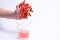 Θηλυκές συμπιέσεις χεριών ενός γκρέιπφρουτ, χυμός γκρέιπφρουτ στο άσπρο υπόβαθρο στοκ φωτογραφία με δικαίωμα ελεύθερης χρήσης