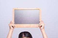 Θηλυκή λαβή χεριών με τον κενό πίνακα κιμωλίας στοκ φωτογραφία με δικαίωμα ελεύθερης χρήσης