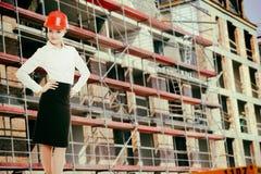 Θηλυκή γυναίκα μηχανικών στο κόκκινο κράνος ασφάλειας στο εργοτάξιο οικοδομής Στοκ Φωτογραφίες