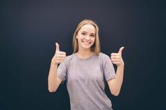 Θηλυκή γυναίκα που παρουσιάζει αντίχειρες επάνω στο σημάδι χεριών στο μαύρο κλίμα Στοκ Εικόνες