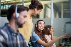 Θηλυκή εκτελεστική αλληλεπίδραση εξυπηρέτησης πελατών με το συνάδελφό της στο γραφείο Στοκ εικόνα με δικαίωμα ελεύθερης χρήσης