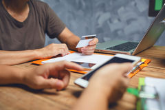 Θηλυκή επιχείρηση που κρατά μια πιστωτική κάρτα για on-line να ψωνίσει από τον όχλο Στοκ Φωτογραφία