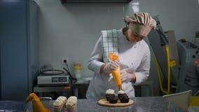 Θηλυκή ζύμη που συμπιέζει ήπια την άσπρη κρέμα γάλακτος κρέμας από μια τσάντα τροφίμων για την έτοιμη σοκολάτα cupcakes, στεμένος απόθεμα βίντεο