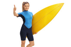 Θηλυκή ιστιοσανίδα εκμετάλλευσης surfer και δόσιμο του αντίχειρα επάνω Στοκ Φωτογραφία