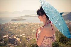 Θηλυκή κινεζική ομπρέλα εκμετάλλευσης και απόλαυση της θέας θάλασσας από το τ Στοκ Φωτογραφίες