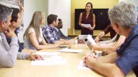 Θηλυκή κύρια εξετάζοντας συνεδρίαση γύρω από τον πίνακα αιθουσών συνεδριάσεων φιλμ μικρού μήκους