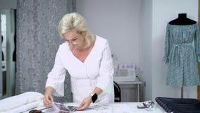 Θηλυκή μοδίστρα που επιλέγει το υλικό από τον κατάλογο στο στούντιο απόθεμα βίντεο