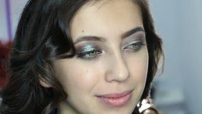 Θηλυκή ομορφιά Στιλίστας καλλιτεχνών Makeup που ισχύει με το καλλυντικό βουρτσών στο φρύδι της νέας γυναίκας απόθεμα βίντεο