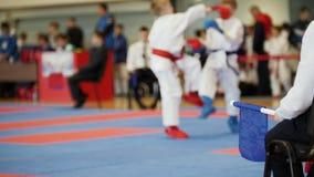 Θηλυκή πάλη karatekas karate στους ανταγωνισμούς, θολωμένο αθλητικό υπόβαθρο φιλμ μικρού μήκους