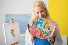 Θηλυκή παλέτα χρώματος εκμετάλλευσης καλλιτεχνών στο στούντιό της Στοκ φωτογραφία με δικαίωμα ελεύθερης χρήσης