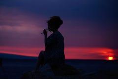 Θηλυκή σκιαγραφία με το κρασί στο ηλιοβασίλεμα Στοκ φωτογραφία με δικαίωμα ελεύθερης χρήσης