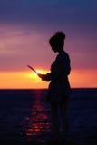 Θηλυκή σκιαγραφία με το lap-top στο ηλιοβασίλεμα Στοκ Εικόνες