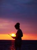 Θηλυκή σκιαγραφία με το lap-top στο ηλιοβασίλεμα Στοκ εικόνα με δικαίωμα ελεύθερης χρήσης