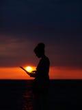 Θηλυκή σκιαγραφία με το lap-top στο ηλιοβασίλεμα Στοκ Φωτογραφία
