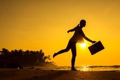 Θηλυκή σκιαγραφία που μένει κατά μήκος της ωκεάνιας ακτής με την τσάντα αποσκευών enj Στοκ Εικόνα