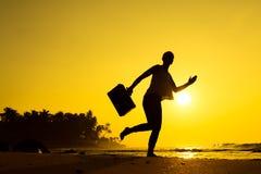Θηλυκή σκιαγραφία που μένει κατά μήκος της ωκεάνιας ακτής με την τσάντα αποσκευών enj Στοκ Φωτογραφία
